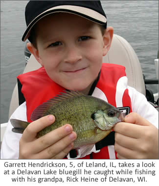 Garrett Hendrickson, 5, of Leland, Ill., takes a look at a Delavan Lake bluegill he caught while fishing with his grandpa, Rick Heine of Delavan, Wis.